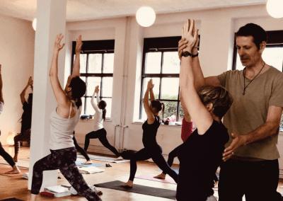 leute im basic yoga kurs - lehrer gibt yogaschulerin hilfestellung